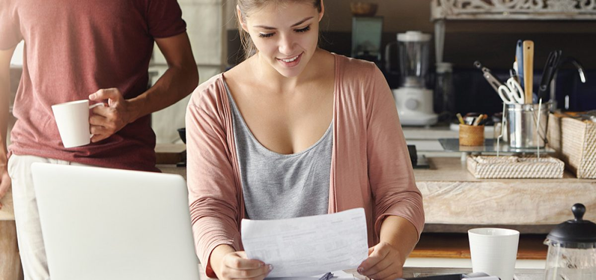 Happy beautiful woman reading notification from bank on prolongation of mortgage term while working through papers at kitchen table with laptop and calculator, her husband standing behind her; Shutterstock ID 587565383; PO: Sam; Job: Refresh; Client: Trulia
