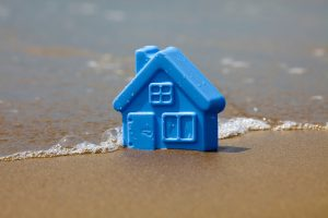 Toy plastic house on the sand washes wave